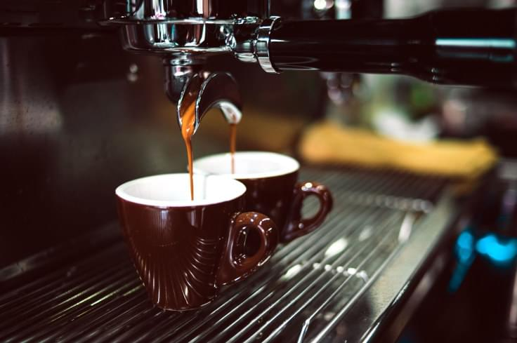 Photo of coffee machine pouring coffee into two cups at the same time by Chevanon